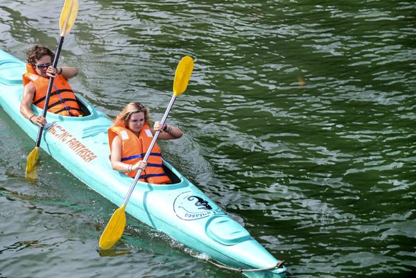 Du khách chèo thuyền kayak khám phá hang động trên vịnh