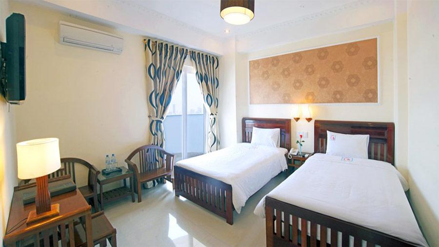 Phòng thường khách sạn Huy Hoàng Hải Tiến với 2 giường đơn 1m6 và 1m2